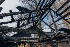 完全地被烧的木房子 倒塌的屋顶残余  火的后果 免版税库存照片
