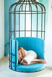 完全地轻松 甜点和舒适梦想,早晨 疲乏的女孩白天睡眠笼子椅子的 现代设计的家具 库存照片