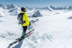 完全成套装备的一个讨便宜者的滑雪者在冰川站立在北高加索以白种人为背景 库存照片