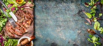 完全油煎的或烤牛排 被切的牛肉seak,服务与蔬菜沙拉叶子和烤肉汁在木切板 免版税图库摄影