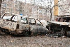 完全被破坏的和损坏的汽车在火烧了在战区或在民用示范接近  免版税库存照片