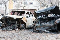 完全被破坏的汽车在火烧了在战区或在民用示范接近  免版税库存照片