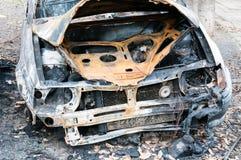 完全被破坏的汽车在火烧了在战区或在民用示范接近  库存照片