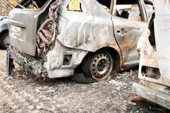 完全被破坏的汽车在火烧了在战区或在民用示范接近  免版税库存图片