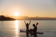 完善的夫妇剪影允诺直立的桨搭乘 库存照片