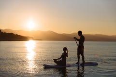 完善的夫妇剪影允诺直立的桨搭乘 图库摄影