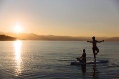 完善的夫妇剪影允诺直立的桨搭乘 免版税库存图片