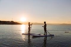 完善的夫妇剪影允诺直立的桨搭乘 免版税图库摄影