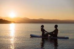 完善的夫妇剪影允诺直立的桨搭乘 免版税库存照片