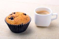 完善的早晨早餐用可口自创杯形蛋糕用葡萄干、巧克力片和浓咖啡咖啡在白色 图库摄影