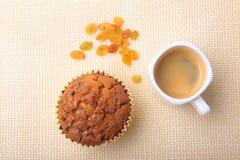 完善的早晨早餐用可口自创杯形蛋糕用葡萄干、巧克力片和浓咖啡咖啡在白色 库存图片