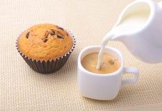 完善的早晨早餐用可口自创杯形蛋糕用葡萄干,巧克力片,在白色杯子的浓咖啡咖啡 免版税库存照片