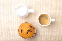 完善的早晨早餐用可口自创杯形蛋糕用葡萄干,巧克力片,在白色杯子的浓咖啡咖啡 免版税图库摄影
