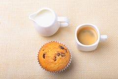 完善的早晨早餐用可口自创杯形蛋糕用葡萄干,巧克力片,在白色杯子的浓咖啡咖啡 库存照片