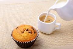 完善的早晨早餐用可口自创杯形蛋糕用葡萄干,巧克力片,在白色杯子的浓咖啡咖啡 库存图片