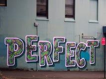 `完善的`,在蓝色墙壁上绘的街道画 免版税库存图片