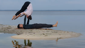 完善的acroyoga 美好的年轻夫妇做着瑜伽 库存图片
