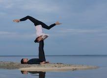 完善的acroyoga 美好的年轻夫妇做着瑜伽 免版税库存照片