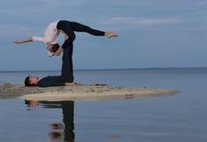 完善的acroyoga 美好的年轻夫妇做着瑜伽 免版税图库摄影
