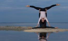 完善的acroyoga 美好的年轻夫妇做着瑜伽 图库摄影