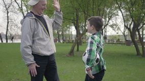 完成一个方格的衬衣和正面老的人的小男孩踢足球在公园 孙子和 股票录像