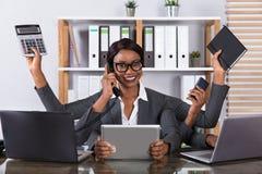 完成在膝上型计算机的疲乏的妇女多任务工作 库存图片