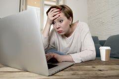 完成在重音看的年轻有吸引力和繁忙的妇女沙发长沙发一些便携式计算机工作在企业家lifes在家担心 免版税库存照片