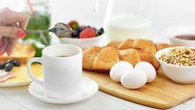 完成女性的手混合热的咖啡使用匙子准备好对有早餐膳食特写镜头 影视素材