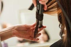 完成她的发型的妇女在美发师 库存照片
