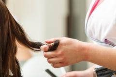完成她的发型的妇女在美发师 免版税图库摄影