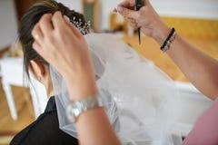 完成她的头发的年轻白种人新娘在她的婚礼那天 库存图片