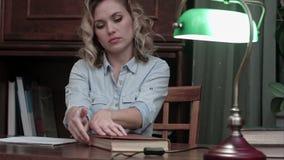 完成她的报告,合上书,关闭灯和留下她的书桌的疲乏的少妇 股票视频