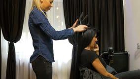 完成她头发的时髦的妇女在美容院,当谈话在手机时 股票录像