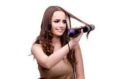 完成她头发的美丽的妇女与吹风器隔绝了o 库存照片