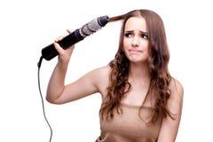 完成她头发的美丽的妇女与吹风器隔绝了o 图库摄影
