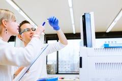 完成实验的两位年轻研究员在实验室 免版税图库摄影