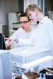 完成实验的两位年轻研究员在实验室 图库摄影