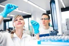 完成实验的两位年轻研究员在浅的实验室 免版税库存图片