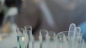 完成测试的实验员在实验室,使用在工作表上的设备 影视素材