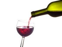 完成瓶-红葡萄酒从绿色玻璃瓶倾吐 免版税库存图片