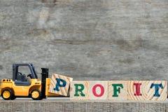 完成词赢利的黄色塑料铲车举行信件P  免版税库存图片