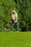 完成高尔夫球运动员他的jupan摇摆 免版税库存照片