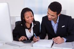 完成财务工作的两个商人 免版税库存图片