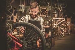 完成他的专业工作的时髦的自行车技工在车间 免版税库存照片
