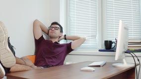 完成他的在他的计算机上的工作和舒展他的胳膊的年轻商人在办公室 休息在办公室 4K 影视素材