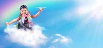 完整色彩的冒险-在云彩的儿童飞行与飞机 免版税库存图片