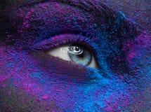 宏指令和特写镜头创造性的构成题材:与干燥油漆尘土颜料的美丽的女性眼睛在面孔,紫色和蓝色颜色 免版税库存照片
