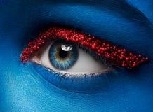宏指令和特写镜头创造性的构成题材:与蓝色油漆的美丽的女性眼睛在面孔和鱼子酱小红色球  免版税库存图片