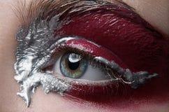 宏指令和特写镜头创造性的构成题材:与银色和红色油漆,被修饰的照片的美丽的女性眼睛 免版税库存照片