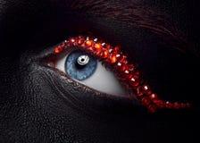 宏指令和特写镜头创造性的构成题材:与黑皮肤和红色金刚石,被修饰的照片的美丽的女性眼睛 免版税图库摄影